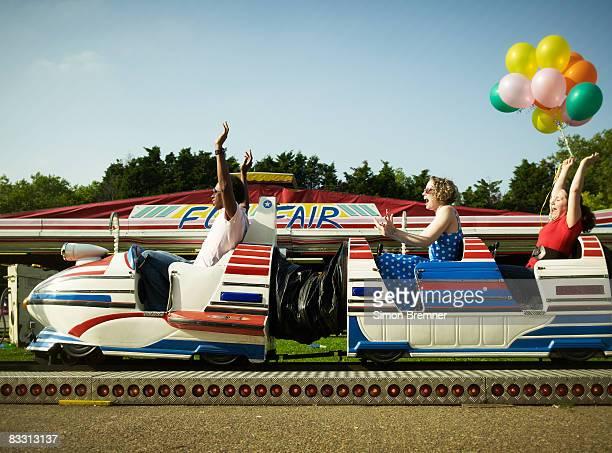 Three people on funfair ride cheering