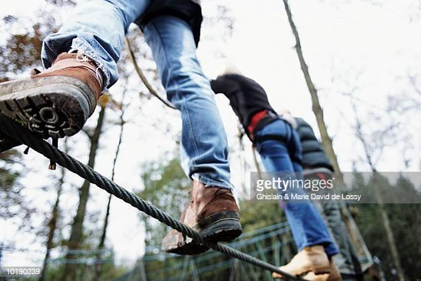 Three people on monkey bridge, low angle view