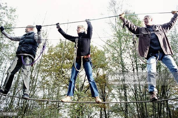Three people on monkey bridge