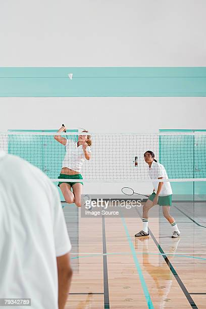 Three people playing badminton
