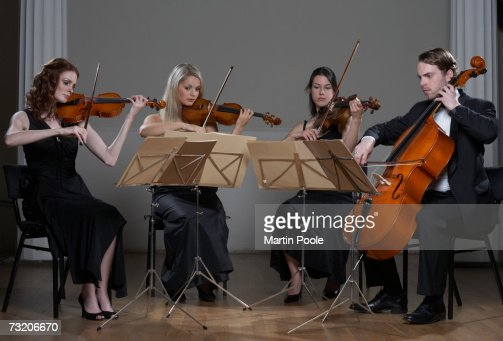 Three people playing violins and one playing cello : Foto de stock