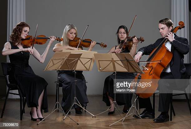 Three people playing violins and one playing cello