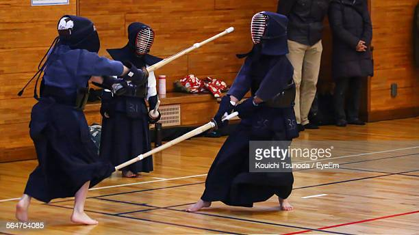 Three People Practicing Kendo