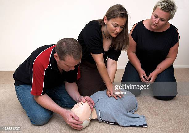 Three people receiving CPR first aid training