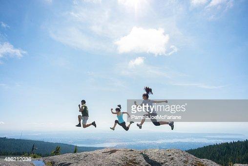 Trois personnes de courir et sauter sur le sommet de la montagne, au bord de la falaise