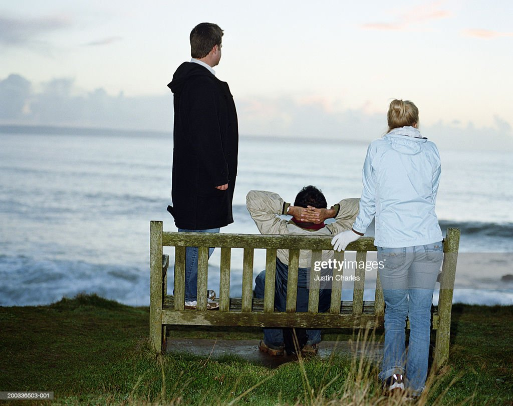 Three people sitting and standing on bench looking out to sea : Stock Photo