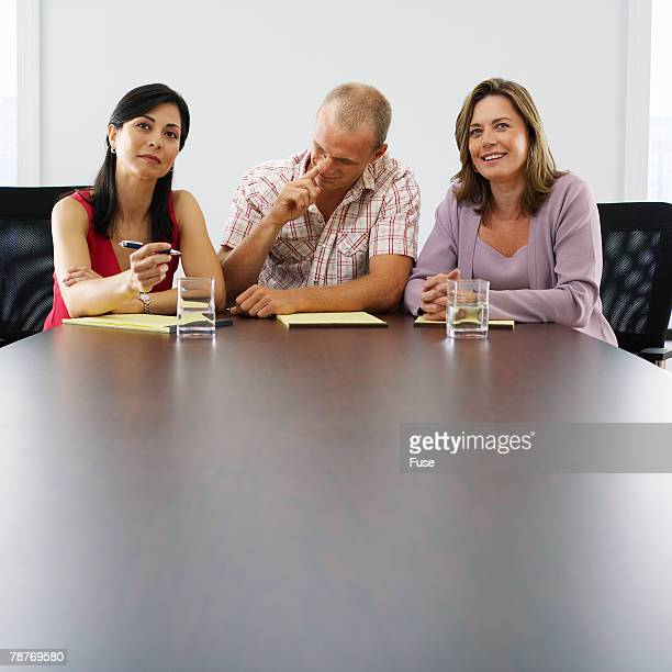 Three People Sitting at Conference Table