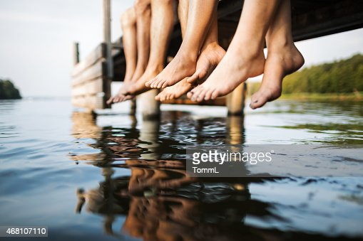 three people sitting on a jetty