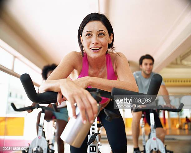 Three people sitting on spinning bikes in gym, close-up