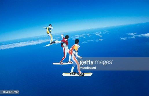 Three people skyboarding against blue sky
