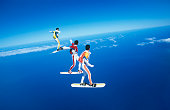 Three people skyboarding against blue sky
