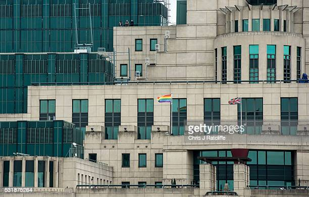 Three people stand on a balcony as a rainbow flag flies outside the MI6 building in support of International Day Against Homophobia on May 17 2016 in...