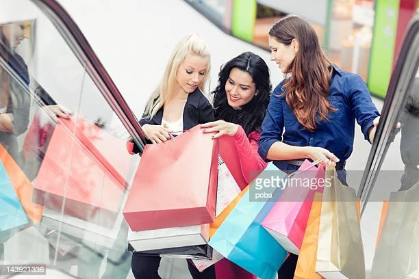 Drei Personen auf Rolltreppe tragen Einkaufstüten