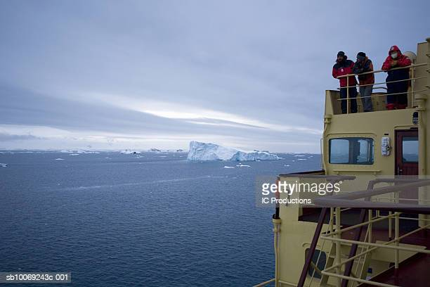 Three people standing on icebreaker ship, looking at view
