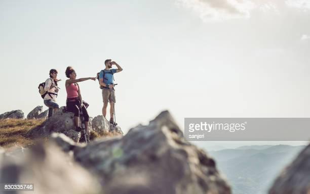 Three People Standing on Top of Mountain