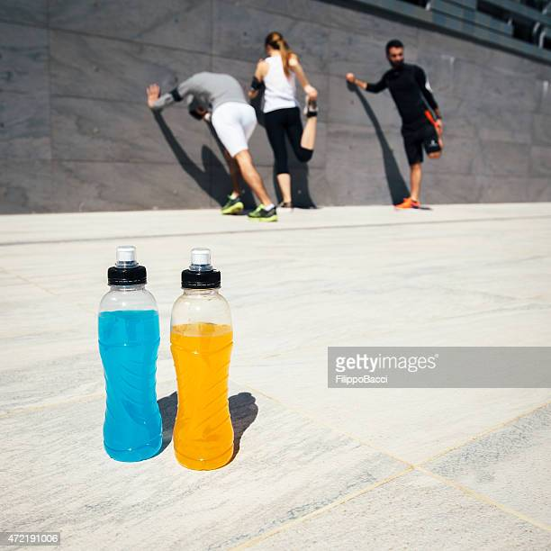 Three people stretching with blue and orange drinks