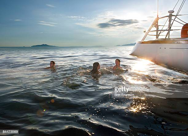 Three people swimming next to sailboat