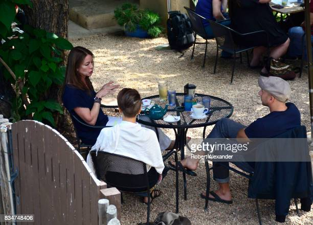 Three people talk over tea and coffee at a Santa Fe New Mexico restaurant with outdoor seating
