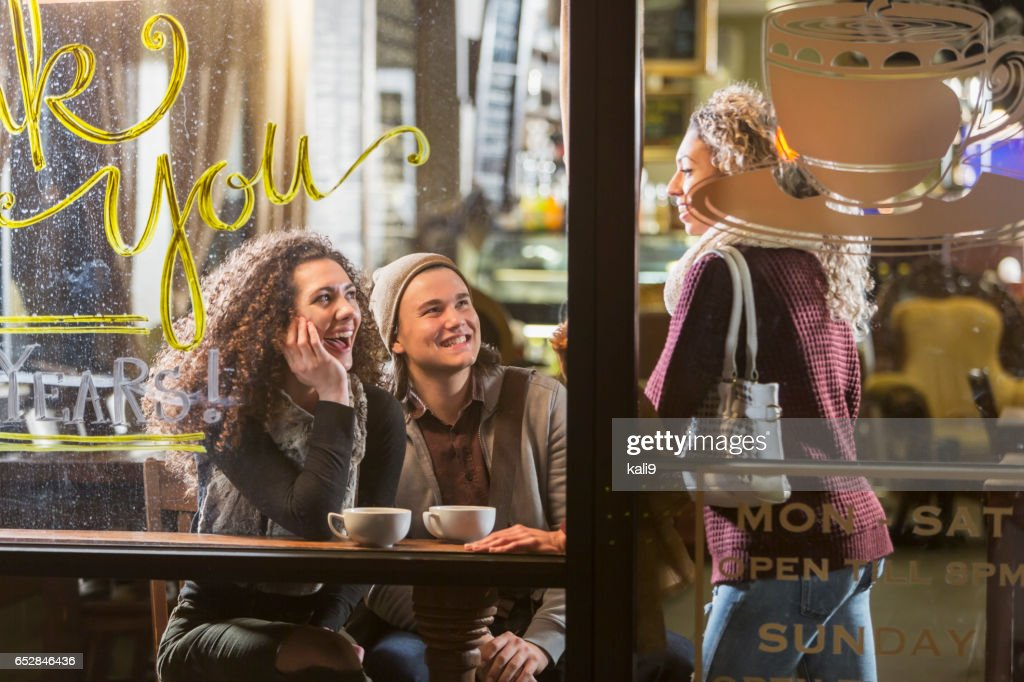 Three people talking in coffee shop : Stock Photo