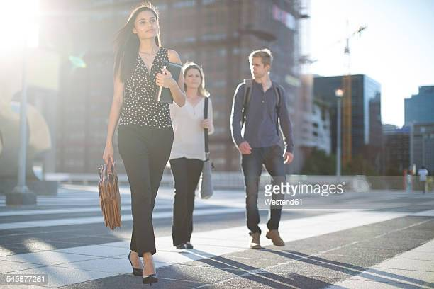 Three people walking on city square