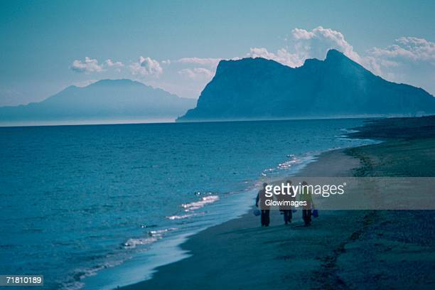 Three people walking on the beach, Rock of Gibraltar, Gibraltar, Spain