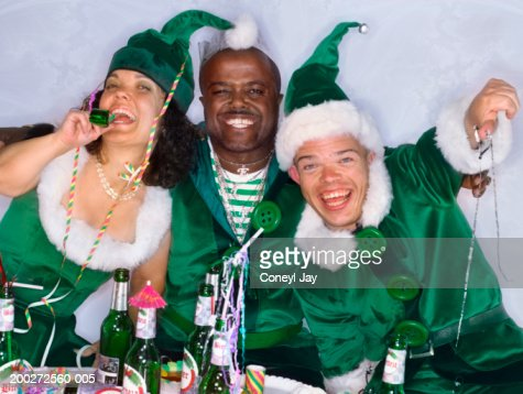 Three people wearing elf costumes at party, smiling, portrait