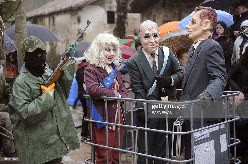 Three people wearing masks representing Spanish king Juan Carlos (2R), his daughter Princess Cristina (2L) and her husband Inaki Urdangarin (R) are carried in a crate during the annual carnival of Zubieta, in the northern Spanish province of Navarra province, on January 28, 2014. The yearly three day festivities, revolving mainly around agriculture and principally sheep hearding, run on the last Sunday, Monday and Tuesday of January where Navarra Valley locals from three villages dress up and participate in a variety of activites in each village as they perform a pilgrimage through each one. AFP PHOTO/ RAFA RIVAS
