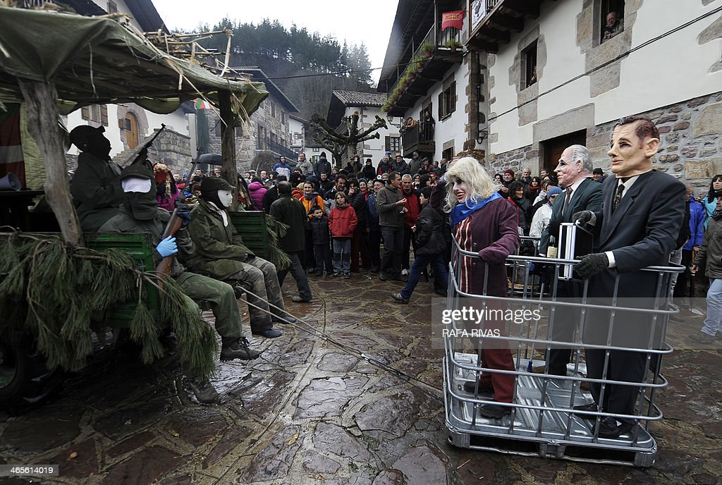 Three people wearing masks representing Spanish king Juan Carlos (2R), his daughter Princess Cristina (2L) and her husband Inaki Urdangarin (R) are carried in a crate during the annual carnival of Zubieta, in the northern Spanish province of Navarra province, on January 28, 2014. The yearly three day festivities, revolving mainly around agriculture and principally sheep hearding, run on the last Sunday, Monday and Tuesday of January where Navarra Valley locals from three villages dress up and participate in a variety of activites in each village as they perform a pilgrimage through each one.