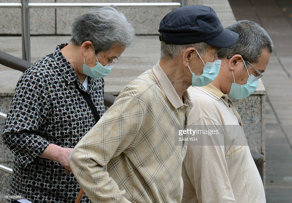 Three people wearing masks walk outside the National Taiwan University Hospital in Taipei on April 25, 2013. International experts probing China's deadly H7N9 bird flu virus said on April 24 it was 'one of the most lethal influenza viruses' seen so far as Taiwan reported the first case outside the mainland. AFP PHOTO / Sam Yeh