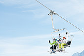 Happy female skiers on ski lift, space for text.