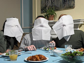 Three people with napkins over faces, at dining table