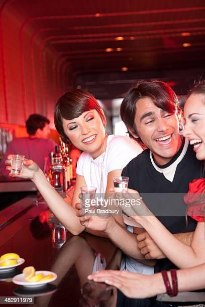 Tre persone in locale notturno sorridente con foto