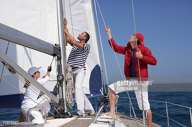 Three people working on a yacht