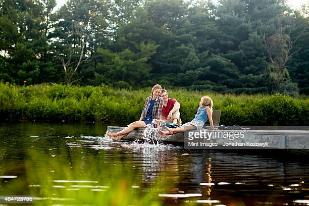 Three people,two adults and a child relaxing on a jetty,with their feet in the water at the end of a day.