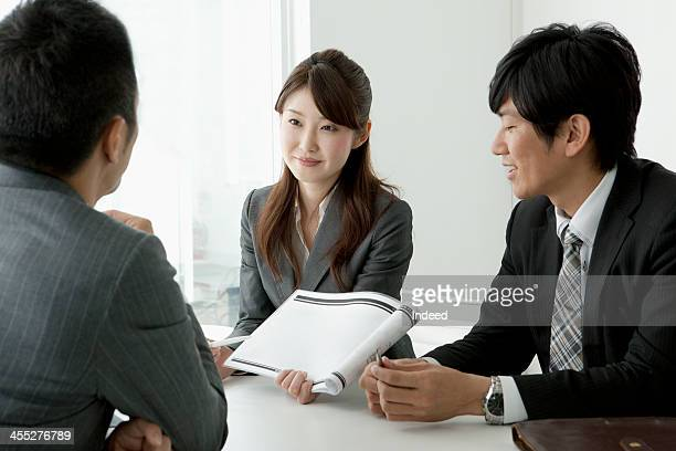 BUSINESS SCENE Three persons in a meeting