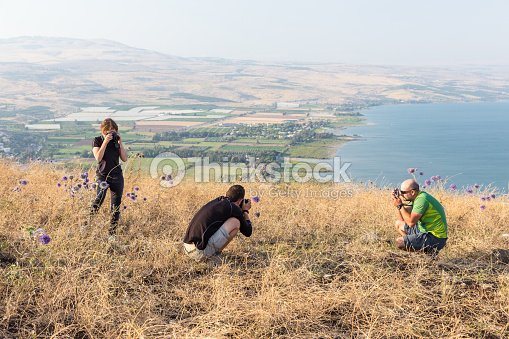Three Photographers Taking Pictures Above Tiberias Lake Stock Photo