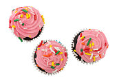 Top view of three pink frosted chocolate cupcakes isolated on a white background.