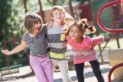 Three playful multiracial children on playground