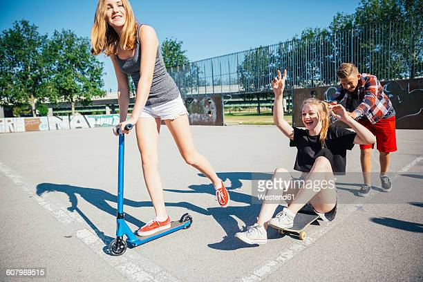 Three playful teenage friends with scooter and skateboard