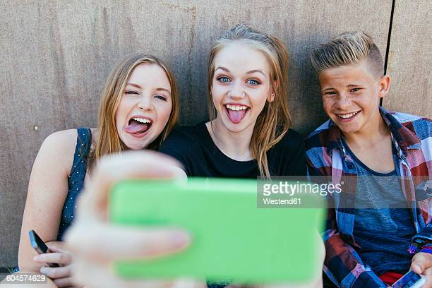 Three playful teenagers outdoors taking a selfie