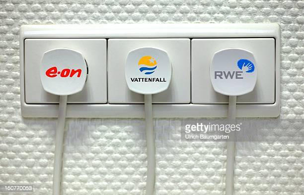 Three plugs with the logos of eon Vattenfall and RWE in different sockets Symbol only very few energy companies dominate the German market