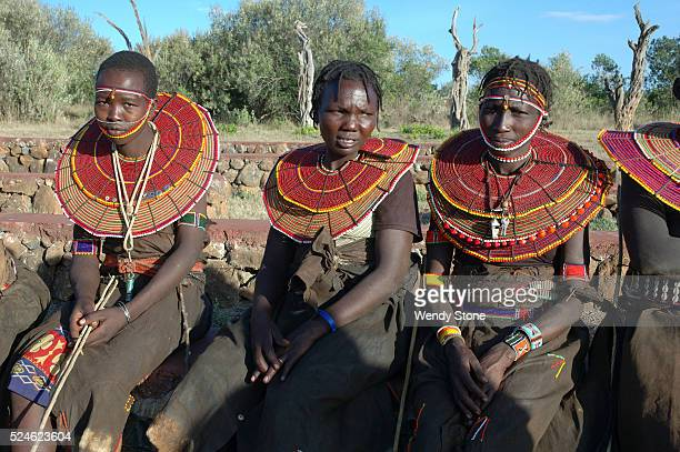Three Pokot women wearing their traditional dress sit at the Earth Festivalat the Laikipia Nature Conservancy The Pokot a small Nilotic tribe live in...