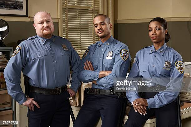 Three police officers in office, portrait