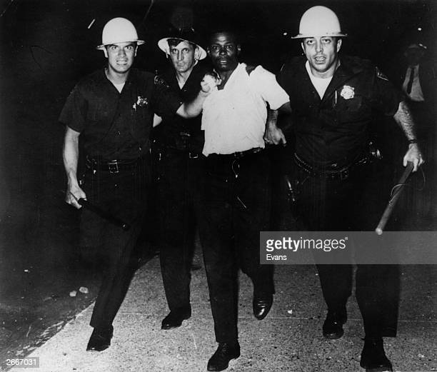 Three policemen taking away a black civil rights protester during race riots in Newark New Jersey