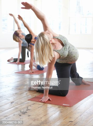 Three pregnant women practicing yoga (focus on woman in foreground) : Stock Photo