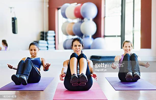 Three pretty women improving core strength with Boat exercise