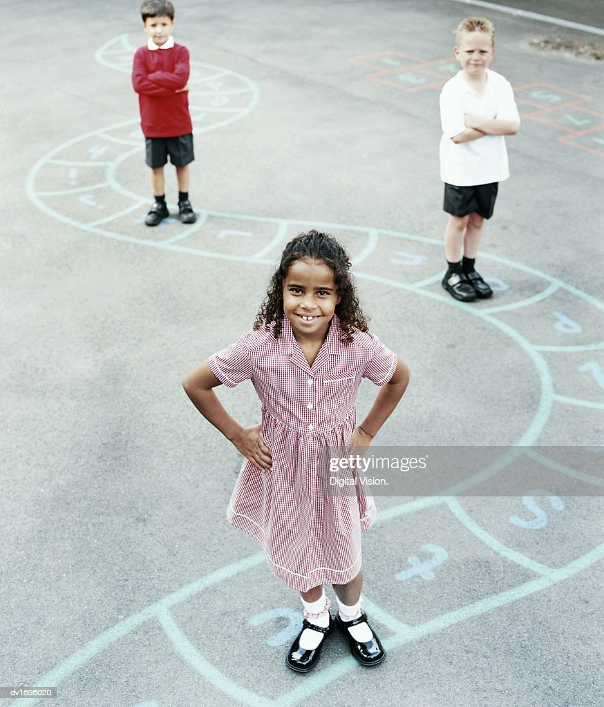 Three Primary School Children Standing on a Chalk Drawing of the Alphabet in a School Playground : Stock Photo