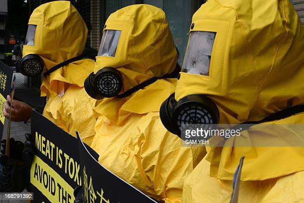 Three protesters dressed in biohazard suits display placards calling the government to help the public to go vegan outside a health department in...