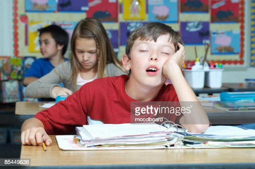 Three pupils in classroom, one of them sleeping : Stock-Foto