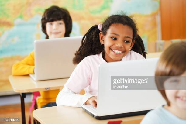Three pupils sitting in a row and using their laptops